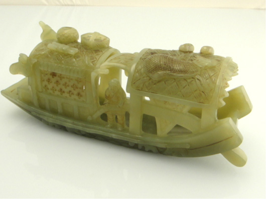 This 7-inch-long celadon jade model of a covered boat is openwork carved with three figures on board with accoutrements atop the roof. It is Lot 50 and expected to command around $2,000. Image courtesy of 888 Auctions.