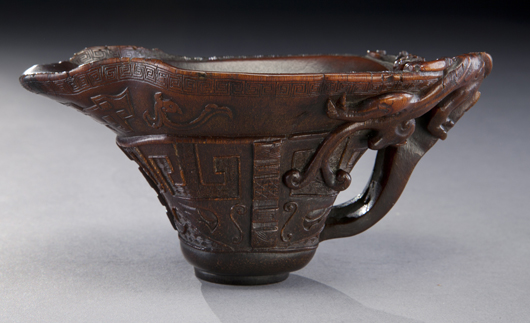 Important Chinese late Ming-early Qing rhinoceros horn libation cup, finely carved to depict chi-dragons, clouds and the face of the beast. Estimate: $150,000-$250,000. Image courtesy of Dallas Auction Gallery.