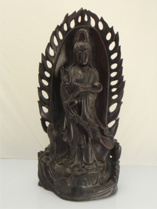 Draped in flowing robes and holding a ruyi scepter in her right hand, the Zitan wood figure of Guanyin is placed prominently in front of a fiery backdrop. Majestic at 19 1/2 inches tall, Lot 419 carries an estimate of $2,000-$3,000. Image courtesy of 888 Auctions.