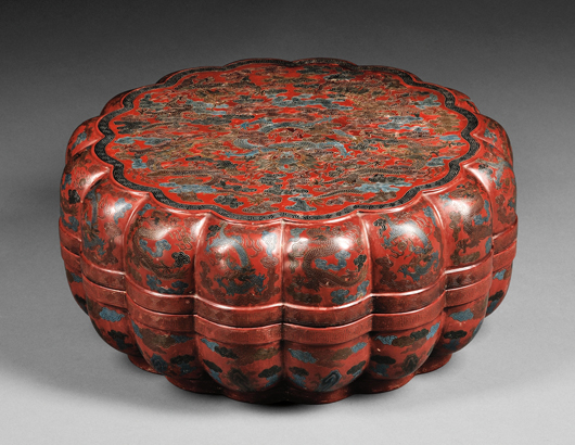 Large lacquer box, China, late 19th century, lobated shape, red lacquer with engraved dragons and clouds, filled in with blue, black, and gold, Ch'ien Lung mark on the base, 15 inches diameter. Estimate $8,000-10,000. Image courtesy of Skinner Inc.