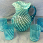 Colorful and early Northwood water set, opalescent blue swirl with four tumblers. Image courtesy of Specialists of the South.