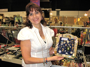 Tammy Vingo holds some of her 'fun' jewelry. Image courtesy of West Palm Beach Antiques Festival.