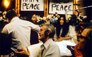 John Lennon and Yoko Ono record 'Give Peace a Chance' in a Montreal hotel in 1969. In the background is a 'Bed Peace' sign that Lennon made. Pictured in the foreground are Timothy Leary (center) and Paul Williams. Photo by Roy Kerwood. This file is licensed under the Creative Commons Attribution 2.5 Generic license.