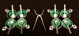 From a Georg Jensen sterling silver flatware set in the Acorn pattern, eight emerald-enameled salts with spoons, and [center] a pair of tongs. Stephenson's Auctioneers image.
