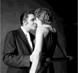 The Kiss, In the privacy of the narrow hallway under the fire stairs of the Mosque Theater (now the Landmark Theater), while other performers are on stage before 3000 fans in the audience, Elvis is concentrating on his date for the day. Mosque Theater, Richmond, Va. June 30, 1956. © Alfred Wertheimer. All rights reserved.