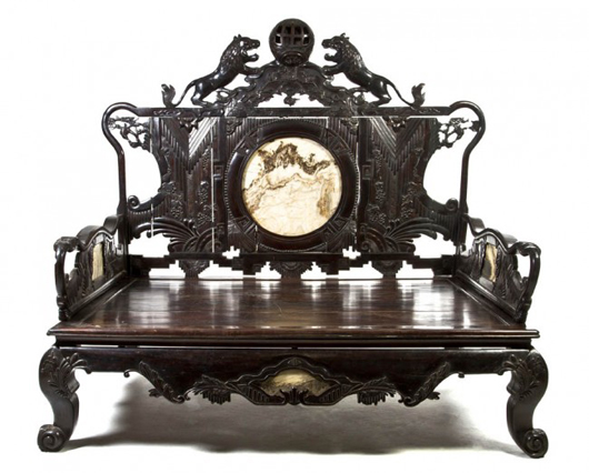 A Chinese carved hardwood opium bed with inset marble panels. Sold for $53,680. Image courtesy Leslie Hindman Auctioneers.