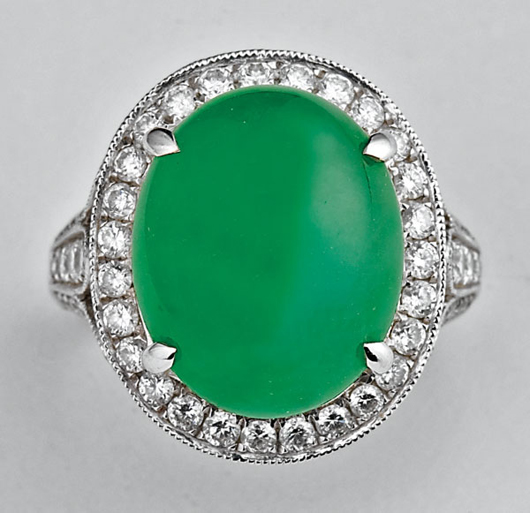 Chinese jadeite cabochon, diamond and 18-karat White gold Ring, translucent apple green oval jadeite cabochon, approximately 12 1/2 carats, diamonds approx. 1.15 carats, size 6 1/2. Estimate: $25,000-$35,000. Image courtesy of Neal Auction Co.