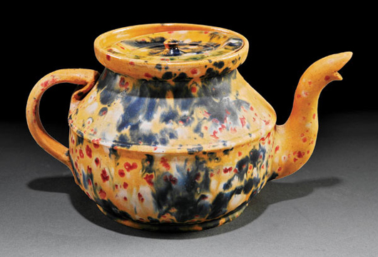 Rare George Ohr art pottery teapot, circa 1883-1898, mustard glaze with mottled green, berry and cobalt slip, inverted lid, base stamped 'G.E. Ohr, Biloxi, Miss.,' height 4 1/2 inches, width 8 1/2 inches. Estimate: $15,000-$25,000. Image courtesy of Neal Auction Co.