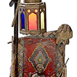 This cold-painted figure depicts an Arab man with a pipe seated in front of a rug and a lit tower. The lamp is 13 inches high and 6 inches wide. It's unmarked but still sold in October 2011 for $763 at Cowan's Auctions in Cincinnati.