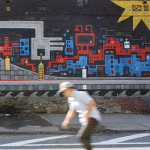 The animated Brooklyn Bridge appears to pick apart the skyline. Mural by Skewville. Photo by Kelsey Savage.