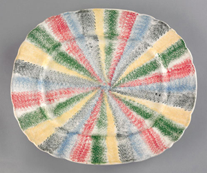 Absolute proof that rarities bring the highest prices, this 13-inch platter decorated with a rainbow of five spatter colors sold for a record $39,780 in April 2009. Courtesy of Pook & Pook