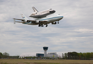 Space shuttle Discovery, mounted atop a NASA 747 Shuttle Carrier Aircraft (SCA) flies over the Steven F. Udvar-Hazy Center, Tuesday, April 17, 2012, in Washington. Discovery, the first orbiter retired from NASA's shuttle fleet, completed 39 missions, spent 365 days in space, orbited the Earth 5,830 times, and traveled 148,221,675 miles. NASA has transferred Discovery to the National Air and Space Museum to begin its new mission to commemorate past achievements in space and to educate and inspire future generations of explorers. Photo Credit: (NASA/Smithsonian Institution/Dane Penland)