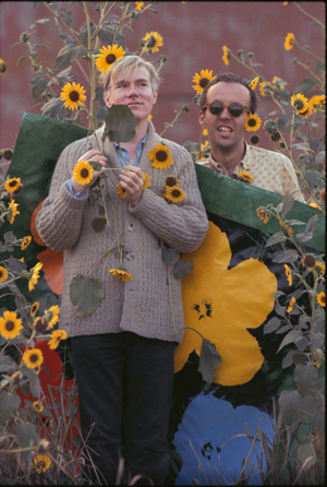 """Andy Warhol in a field of black-eyed Susans with Taylor Mead holding an early """"Flowers"""" canvas as a backdrop in Queens, New York. Title: Warhol Flowers VII Location: Flushing, Queens Medium: Chromogenic Print Edition: 60 with 7 Artist Proofs Size: 24 x 16 inches Executed: 1964 Printed: 2012 Copyright 2010 William John Kennedy / Courtesy of Kiwi Arts Group"""