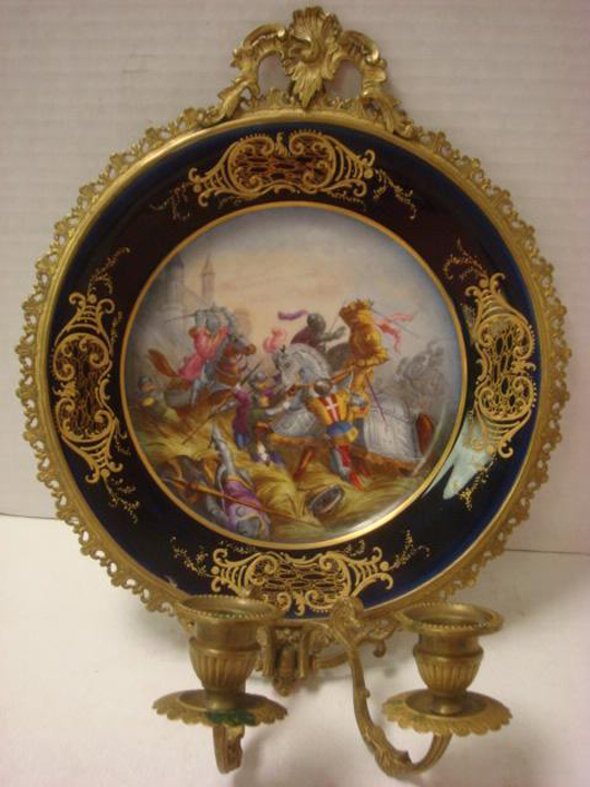Sevres hand-painted plate in gilt candleholder frame, pierced bronze or brass frame with double candleholders,1846, 10 1/4 inches diameter. Estimate: $1,500-$3,000. Image courtesy Phoebus Auction Gallery.
