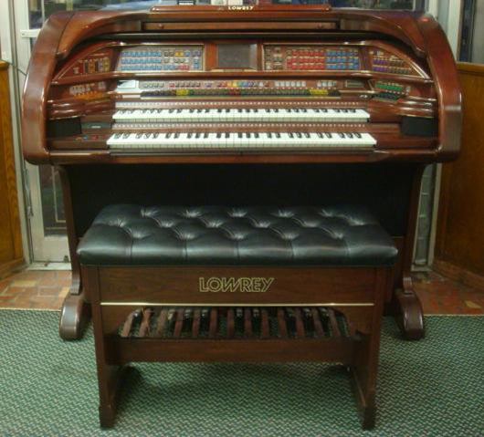 Lowrey Cherry Stardust organ with bench, Model SU-530, color touch LCD screen, 600 song titles. List price: $60,000. Estimate: $20,000-$40,000. Image courtesy Phoebus Auction Gallery.