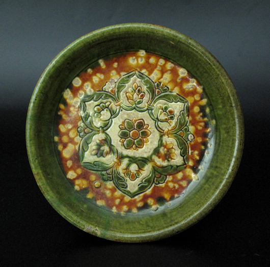 Chinese Sancai glazed tripod tray, offering dish, with floral pattern, Tang Dynasty, 8.4 inches diameter. Estimate: $10,000-$20,000. Image courtesy Joyce Gallery Auction.