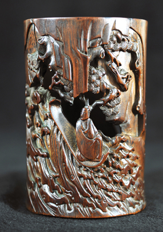A detailed scene of Bodhiharma crossing the Yangtze on a stalk is carved on the exterior of this bamboo brush pot having a 'San Song Zhi' mark. Estimate: $120,000-$200,000. Image courtesy Golden State Auction Gallery.