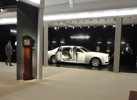 Ancient and modern — a long case clock stands opposite a Rolls Royce Ghost at the 21012 Masterpiece fair in Chelsea, London this week. Even the car's trunk has a lambswool lining to 'cosset' custom luggage. Photo Auction Central News.