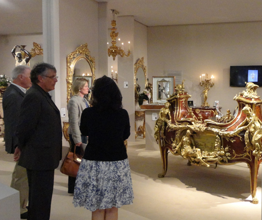 Visitors to London's Masterpiece fair admire a rococo Revival bureau by 19th century French ébéniste François Linke on the stand of London dealer Adrian Alan. Photo Auction Central News.