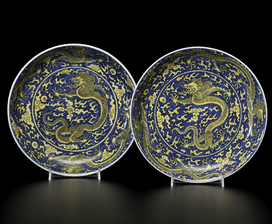 A pair of Chinese porcelain dragon chargers, Kangxi mark and period. The interior bowl and exterior rim having five-clawed dragons chasing a fiery pearl surrounded by wispy clouds in yellow on a blue ground, with six-character Kangxi mark within double rings in sharp blue on underside, housed in a two-drawer box. Estimate: $30,000-$40,000. Cowan's Auctions Inc. image.