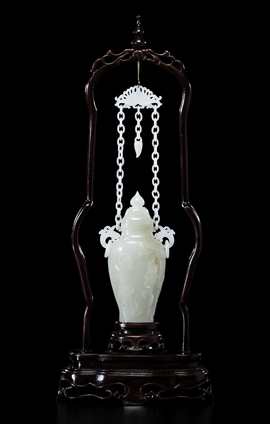 A 20th century Chinese white jade lidded vase carved with flowers, having two handles with drop rings, connecting to a chain with a lotus flower, all suspended on a wooden frame. Estimate: $10,000-$12,000. Cowan's Auctions Inc. image.