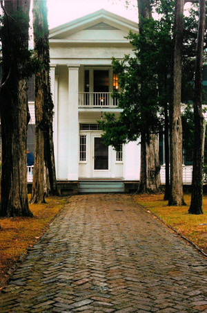 """Front walk and entrance of Rowan Oak, the home of Nobel laureate and American novelist William Faulkner in Oxford, Mississippi. It is now owned and maintained by the University of Mississippi as a museum. One of the oldest structures in Oxford, this Greek Revival house on Old Taylor Road was built in the 1840s by a Colonel Shegog. Faulkner bought the crumbling house, then known as the """"Bailey Place,"""" in 1930. He promptly renamed it and slowly refurbished the property. Faulkner's daughter sold Rowan Oak to the university in 1972. It is a National Historic Landmark. Photo by Gary Bridgman, licensed under the Creative Commons Attribution 2.5 Generic license."""