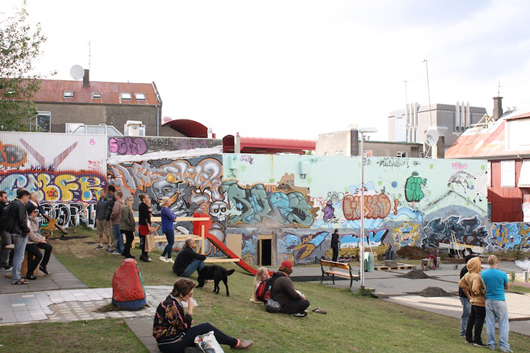 While some individuals socialize, others are building a patio. Street art by unknown artist, Reykjavik, Iceland. Photo by Kelsey Savage.