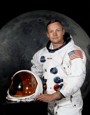 Portrait of Astronaut Neil A. Armstrong (American, 1930-2012), commander of the Apollo 11 Lunar Landing Mission in his space suit, with his helmet on the table in front of him. Behind him is a photograph of the lunar surface. NASA Photo No. S69-31741, taken July 1, 1969.