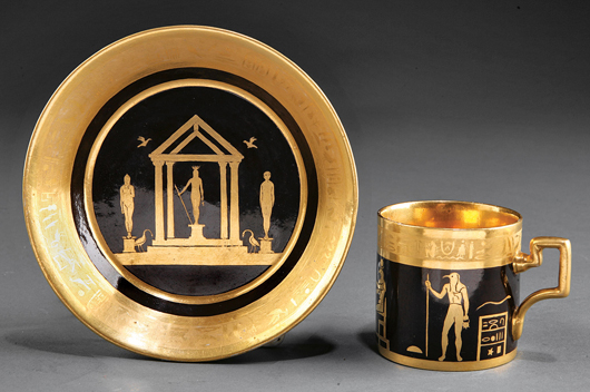 Enhanced by an intricate gilt border, this Paris porcelain cup and saucer with Egyptian deities against a dark ground brought $837 at auction. Courtesy Neal Auction Co.