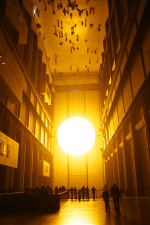 Olafur Eliasson's better-known installations include 'The Weather Project,' 2003, at Tate Modern in London. Eliasson used humidifiers to create a fine mist in the air via a mixture of sugar and water, and installed a semicircular disc composed of hundreds of monochromatic lamps that radiated yellow light. Photo by Thomas Pintaric, licensed under the Creative Commons Attribution-Share Alike 3.0 Unported license.
