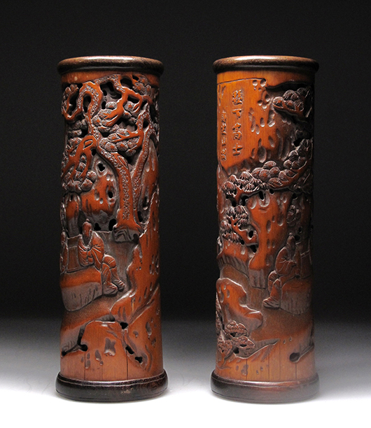 Pair of Chinese carved bamboo incense cylinder, carved with continuous landscape of figures conversing and playing games beneath a large openwork pine tree. 25 centimeters high by 8.2 centimeters diameter. Joyce Gallery Auction image.