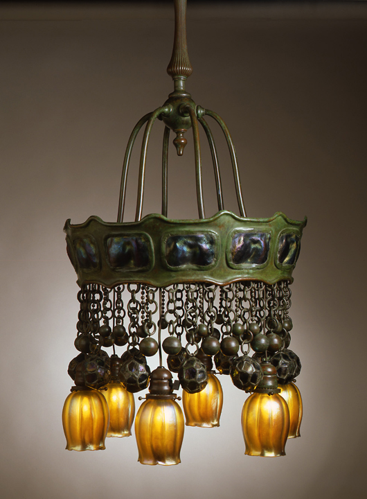 The Neustadt Collection also contains a number of hanging lamps. This exotic electric chandelier features iridescent turtleback glass panels inset in the bronze crown and Favrile shades over the lights suspended below. Courtesy Neustadt Collection of Tiffany Glass