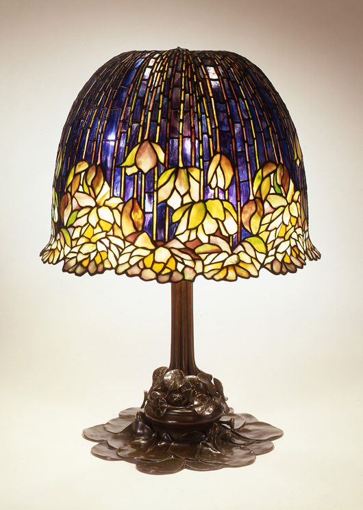The Neustadt Collection of Tiffany Glass organizes touring exhibitions which dazzle viewers and offer collectors in-depth information about how the beautiful lamps were constructed.  A tour-de-force creation on display in the current show, this pond lily library lamp juxtaposes a cascading glass shade above a base of supporting lily pads.  Courtesy Neustadt Collection of Tiffany Glass