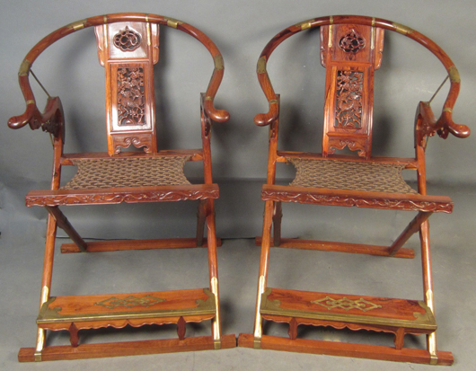 Pair Chinese hardwood folding chairs with brass hardware, cloth woven seats and ornately carved splats. Most likely huanghuali wood. Sterling Associates image.