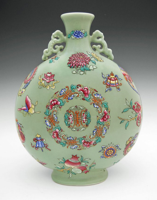A marquee item, the Famille Rose pea-green ground moon flask features a stylized peony medallion at the center with Shou characters encircled with eight Buddhist emblems. The handles are Qilin form. Gianguan Auctions image.