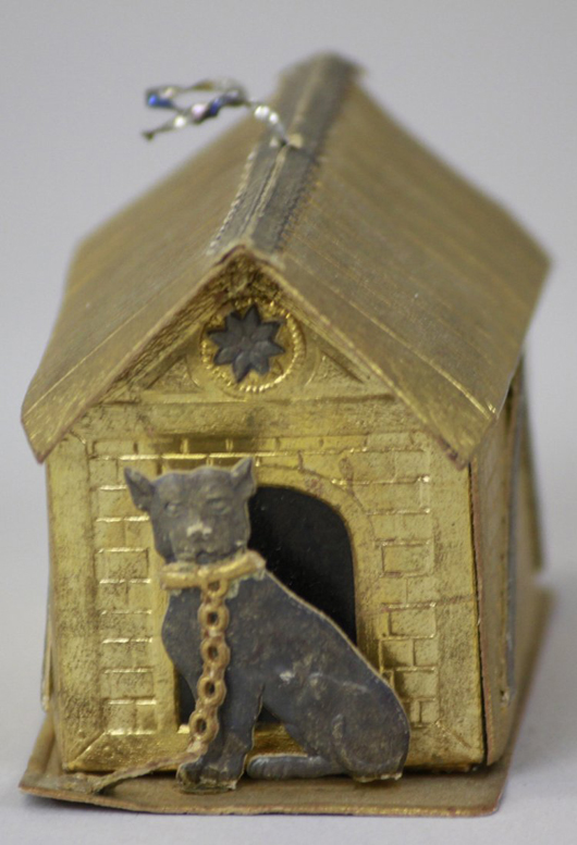 A fine example of an early German Dresden ornament, depicts a chained dog sitting in front of a gilt cardboard doghouse. Doubling as a candy container, its roof lifts off to allow access to candy. Collection of Catherine Saunders-Watson.