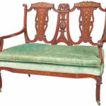 Mahogany with mother-of-pearl inlay was used to make this 1910 Edwardian settee. The back, with open spaces and scrolls, and the seat pad are typical of the period. It auctioned for only $344 at a Doyle New York auction last summer.