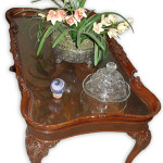 A piece of custom cut glass has protected the crotch mahogany top of this Depression-era coffee table from dustables, kids, pets and general wear for 30 years.