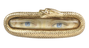 A portrait of a pair of blue eyes and eyebrows is in the center of this antique 'lover's eye' brooch. A gold snake is curled around the edge of the frame. The brooch sold for $2,280 at a Skinner auction in Boston.