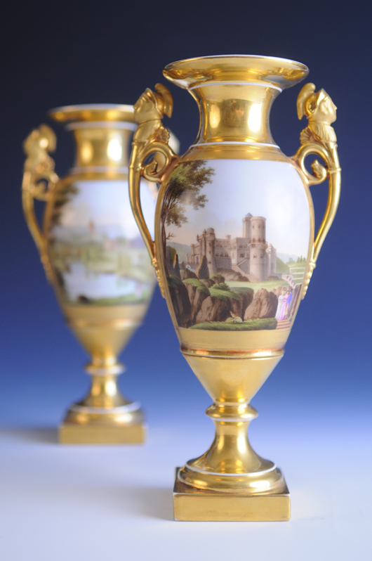 Pair of German porcelain twin-handled vases, possibly Gotha, circa 1820-30, hand-painted veduta to each side depicting the Schloss Wilhelmshöhe and Löwenburg Castle in Kassel. Sworders image.