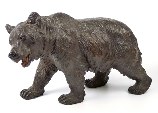 Black Forest bear, late 19th century, carved four-square looking to the left, open mouth and painted red and orange details, 49cm. Estimate: £400-£600. Sworders image.