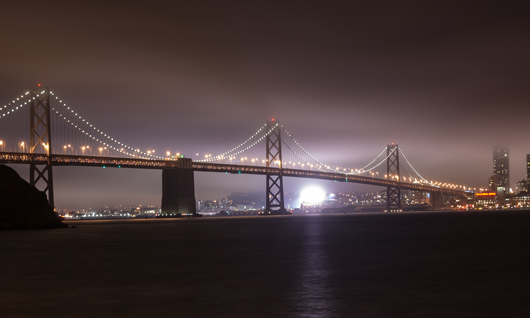 The standard lighted bridge under fog as seen from Treasure Island. Image by Nitesh Aggerwal. This file is licensed under the Creative Commons Attribution-Share Alike 3.0 Unported license.