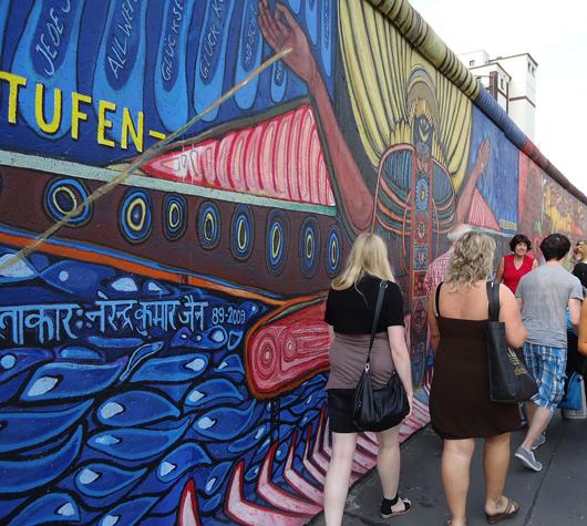 Kunstenthusiasten schlendern entlang der East Side Gallery in Berlin, einem kleinen Reststück der Berliner Mauer gewidmet als Freiluftgalerie. Foto von Heidi Lux