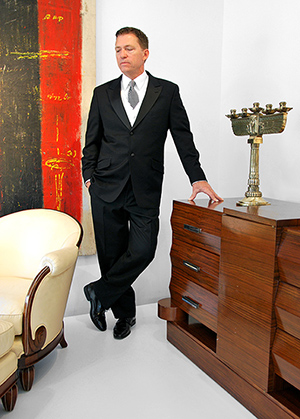Palm Beach Modern's auctioneer, Rico Baca, gets into the Gatsby mood as he inspects premier items in the company's May 25 auction, including (clockwise from left) one of a pair of Jules Leleu French Art Deco period chairs with ottomans, a large Jeff Compertz abstract painting, one of a pair of circa-1930 French Art Deco Egyptian Revival candelabra, and an Alfred Porteneuve French Art Deco rosewood with silver-plated bronze sideboard/dresser made in 1939 for the SS Pasteur ocean liner. Palm Beach Modern Auctions image.