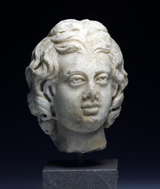 Roman marble head of Eros, Antonine Period, est. $15,000-$20,000. Antiquities Saleroom image.