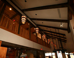 The industrial salvaged timbers with original patina adorn the ceiling and frame the loft area of the restaurant.