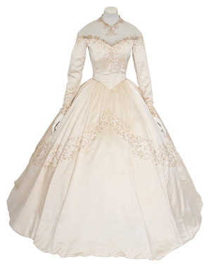 An important wedding dress worn by Elizabeth Taylor for her first wedding to Conrad 'Nicky' Hilton, 1950, the oyster silk satin wedding dress designed by M.G.M. chief costume designer Helen Rose, the satin dress with fine silk gauze off-the-shoulder illusion neckline, the sleeves long and fitted, with a train, the neckline, bodice, cuffs and skirt embroidered with simulated seed pearls and glass bugle beads in a foliate motif, together with a long silk tulle veil with beaded Juliet cap; accompanied by a document concerning the provenance and a photograph of the vendor wearing the dress at her own wedding. Estimate: £30,000 – 50,000. Price Realized in June 26, 2013 auction held at Christie's South Kensington:: £121,875/$187,931/€143,569. Image courtesy Christie's Images Ltd.