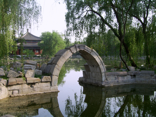 The pavilion and stone arch bridge are among the few remaining original structures at The Old Summer Palace in Beijing. Photo by Shizhao, licensed under the Creative Commons Attribution-Share Alike 2.5 Generic license.
