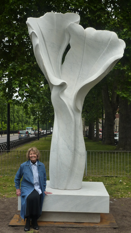 Cambridge-based sculptor Helaine Blumenfeld, sitting beside her 2007 work titled 'Spirit of Life,' recently installed on a plinth near the Dorchester Hotel in Park Lane. Image courtesy of Helaine Blumenfeld and Robert Bowman Ltd., London.