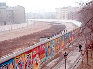 The Berlin Wall has served as a canvas for graffiti art for several decades. This photograph shows the West Berlin side of the wall. The east side of the wall, previously known as the 'death strip,' follows the curve of the Luisenstadt Canal, which was filled in 1932. Photo taken in 1986 by Thierry Noir, licensed under the Creative Commons Attribution-Share Alike 3.0 Unported license.